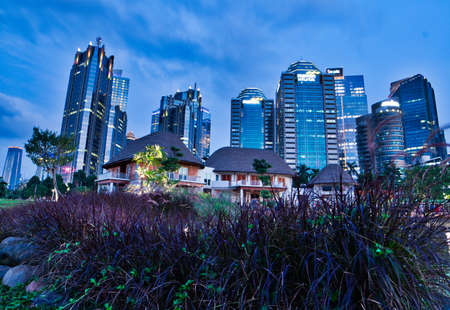 Jakarta, Indonesia, March 2, 2019 : Cityscape in Mega Kuningan metropolitan building with some of white house and purple flower Sajtókép