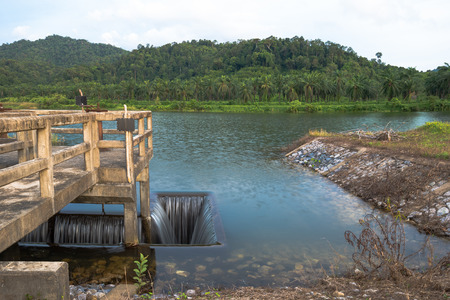 Ditch inlet of weir water gate infrastructure. Overflow from lake to palm plantation and irrigation Stock Photo