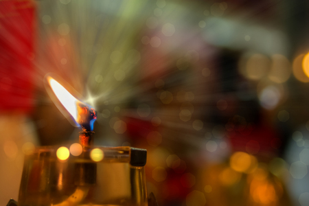 chinese holly: Oil lamp with bokeh and blurred background. Oil lamp burns brightly at shrine ,vegetarian festival, Phuket Stock Photo