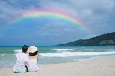 sun hat: Happy mature couple sitting  on white sand beach  enjoying rainbow. Lovely wife with sun hat and husband  sat together on the beach..Happy wife with sun hat and husband  sat together at the beach. Stock Photo