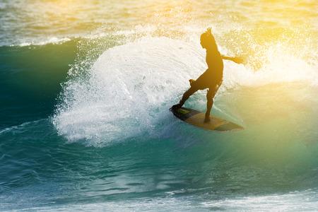 iluminado a contraluz: Silueta de surf Feliz surfista disfrutar de una gran ola y espuma al atardecer Foto de archivo