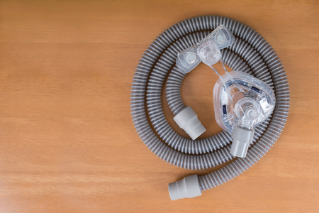 Pair of CPAP mask and tubing. Cleaning cpap mask and tubing is a routine job,flat lay. Stock Photo