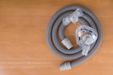 Pair of CPAP mask and tubing. Cleaning cpap mask and tubing is a routine job,selective focus on cpap mask,flat lay Stock Photo