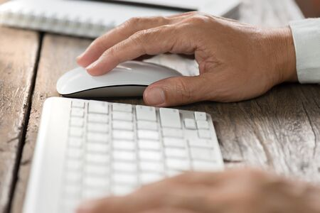 Never easy like tthis before. Man hands using wireless mouse and keyboard on old wooden table. Stock Photo
