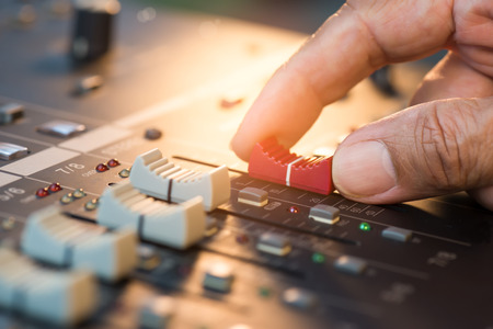 Hand adjusting volume fader of digital audio mixer. Professional sound engineer balancing volume of audio inputs in concert,bokeh background