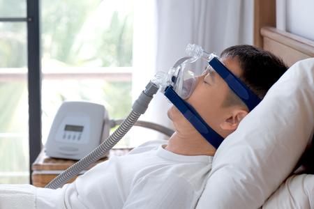 閉塞性睡眠時無呼吸症候群治療、日の休憩中に cpap とマシンを使用している人。 Cpap 陽性気道圧。簡単に帽子のマスクを身に着けているいびき睡眠