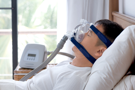 Obstructive sleep apnea therapy, Man using CPAP machine during day break. CPAP Continuous positive airway pressure .Happy middle age man breathing more easily during sleep without snoring wearing headgear mask.