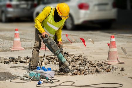 Jackhammer와 구체적인 차도를 시추하는 작업자. 무거운 의무 기계 도로 표면을 복구하는 사람 (남자).