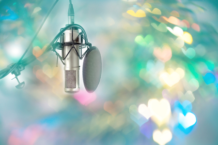Microphone setting ready for DJ in celebration party valentine day. Colourful heart  bokeh in front of microphone ,retro style. Stock Photo