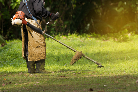 grass cutting: Close up of man holding grass trimmer.  Worker mowing lawn with  garden gasoline trimmer rotating left and right.