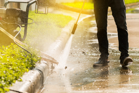 High pressure deep cleaningWorker cleaning driveway with gasoline high pressure washer,sunlight background.