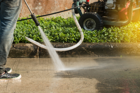 High pressure deep cleaning.Worker cleaning driveway with gasoline high pressure washer with sunlight .