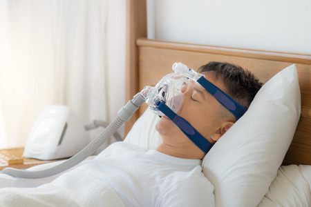 Obstructive sleep apnea therapy, Man wearing CPAP mask. CPAP:Continuos positive airway pressure  therapy.Happy and healthy senior man breathing more easily during sleep  on his back without snoring. Stock Photo
