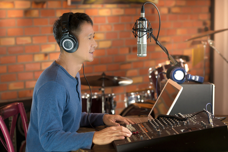 DJ working at radio broadcasting studio,hands adjusting volume and keyboard. Male radio broadcaster using laptop computer and audio mixer controlling his  live radio program. Stock Photo