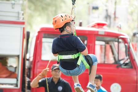 Phuket-January 14,2017:Zip-line for child play on children day activity at Sapanhin park. Brave children zip lining with happy smiling face from the truck top with fully security equipment.
