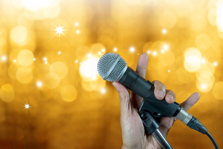 Hand holding microphone on stand with bokeh glow blurred background. Singer on karaoke stage party.