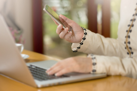 Close-up of  modern business woman hands using smart phone and   laptop computer.Connect and type  with bokeh and blurred background.