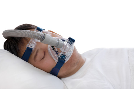 Sleep apnea therapy, Man sleeping in bed wearing CPAP mask.Healthy senior man sleeping deeply, happy on his back without snoring,isolated white background Stock Photo