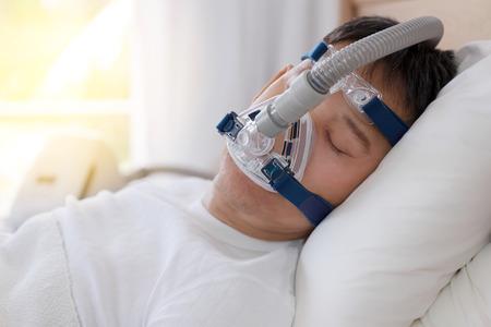 Terapia apnea del sonno, uomo che dorme nel letto indossando maschera CPAP. Senior uomo anziano che dorme profondamente, felice sulla schiena senza russare Archivio Fotografico - 82806815
