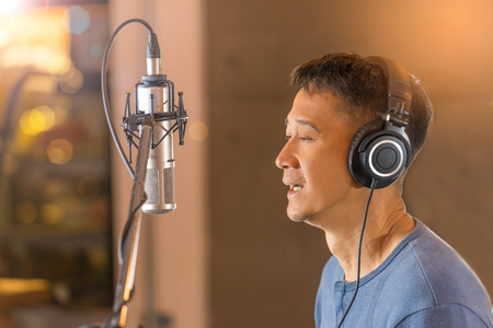 Man singing in front of recording microphone.Male singer wearing headphone during voice recording in studio,bokeh background