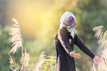 Healthy beautiful woman  breathing deeply at  sunrise in highland mountain with arms open.Woman in black dress with hair scarf inhaling fresh air and sunbathe early morning light . Фото со стока