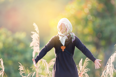Healthy beautiful woman  breathing deeply at  sunrise in highland mountain with arms open.Woman in black dress with hair scarf inhaling fresh air and sunbathe early morning light . Stock Photo