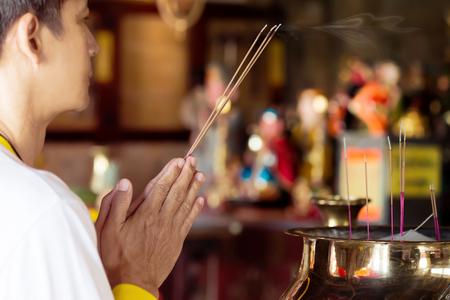男は、仏様に線香を照明の新年の祈り。 中国の新年祭でメリットを作るため中国神社線香と油ヤシのキャンドルを燃焼します。 彼の人生は、健康と