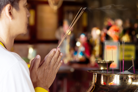 combustible: Man praying for new year ,lighting incense to Buddha. Burning joss stick and oil palm candle at chinese shrine for making merit in chinese new year festival.  May his life be blessed with health  and happiness all through.