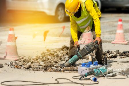 労働者は削岩機と具体的な私道を掘削します。 ヘビーデューティ マシン、日光で路面を修復する男。