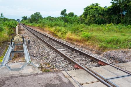 鉄道。   鉄道とタイの田舎の公道と交差する点。 写真素材