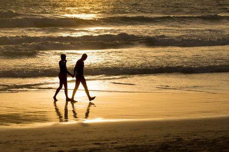 二人は、黄金のビーチと海のボケ味に手をつないでと裸足を歩いて夕暮れ時のシルエット。 夢の島での素晴らしい休暇のための生命のロマンチック