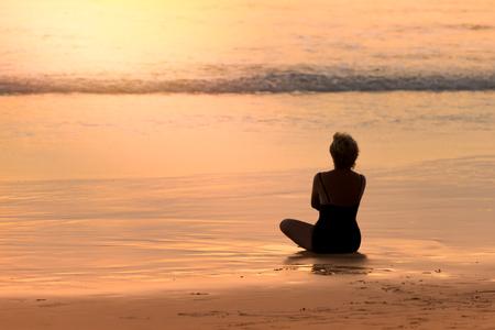 夕日で黄金のビーチと海のボケ味に座っている女性のシルエット。 素晴らしいビーチの静かなあなたの魂に自由を返します。