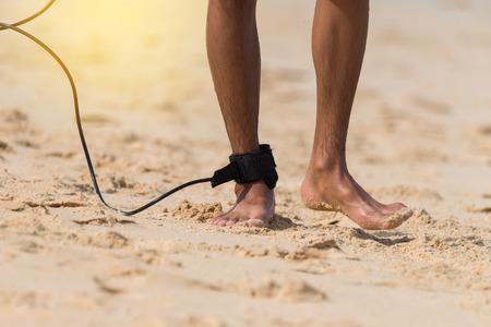 ビーチの上を歩いて足にロープでアジアの若いサーファー。 晴れた日と大きな波、サーファーの楽園。