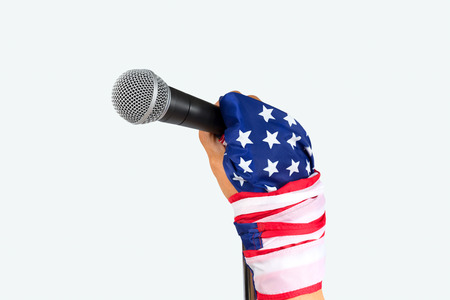 United states of America spokesman said.  Hand with flag wristband holding microphone,isolated white background.