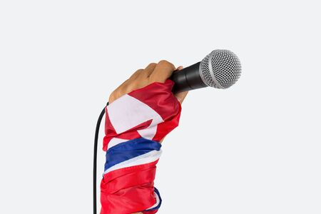 North Korea spokesman said.  Hand with flag wristband holding microphone,isolated white background.