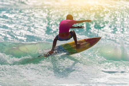 夕暮れサーフィン シルエット。 幸せなサーファーは、熱帯の島での休暇中にビッグ ウェーブをお楽しみいただけます。