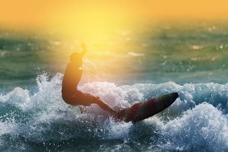 夕暮れサーフィン シルエット。 幸せなサーファーは、熱帯のビーチでの休暇中にビッグ ウェーブをお楽しみいただけます。
