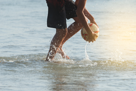 夕暮れ時、海からボールを拾いの少年。 ビーチ サッカー、熱帯のビーチでの素晴らしい休暇中に家族の活動。