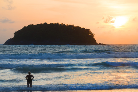 夕日で黄金のビーチに大きな波に対して立っている女性のシルエット。 素晴らしいビーチの静かな自由をあなたの魂は、旅行目的地、プーケットに