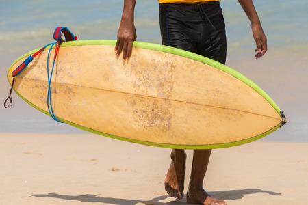 アジアのサーファーがビーチに来るサーフボードを運ぶします。 水スポーツ活動晴れた日の熱帯のビーチでの休暇中に。 写真素材