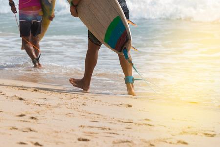 歩いて海にサーフボードを運ぶ足ロープで若いサーファー。 晴れた日、ビッグ ウェーブ、熱帯のビーチでの休暇中にサーファーの楽園。 写真素材