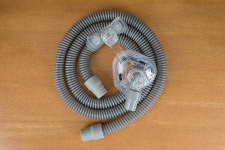 Pair of CPAP mask and tubing. ,selective focus on cpap mask,flat lay. Parts of Cpap machine for obstructive sleep apnea therapy.