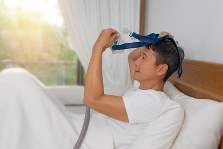 人間は、睡眠時無呼吸症候群治療、cpap とマスクを身に着けているベッドに横たわっていた。 幸せで健康な男、閉塞性睡眠時無呼吸や呼吸障害、連
