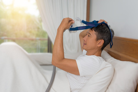 Man lay in bed wearing CPAP mask ,sleep apnea therapy. Happy and healthy man,Obstructive sleep apnea or breathing disorder ,wearing CPAP mask for a continuous sleeping. Stock Photo