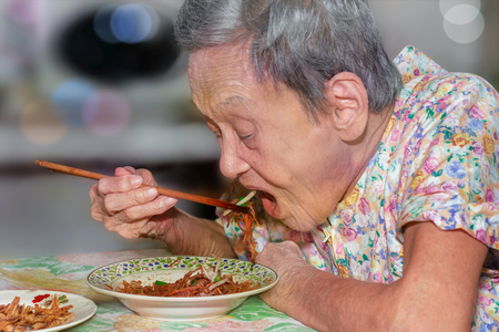 Portrait of a happy elderly woman in colorful dress opening mouth wide eating noodle with chopsticks by herself. 90 up of healthy woman having lunch,side view.