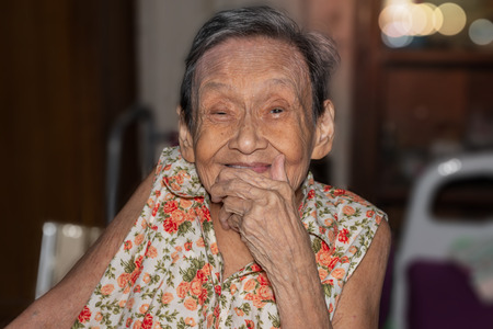 Portrait of a happy elderly woman in colorful dress smiling while sitting in home. 90 up of healthy woman,front view. 스톡 콘텐츠