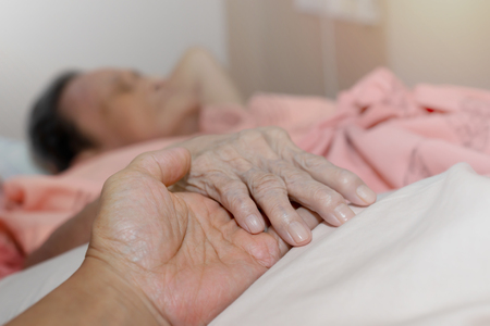 Close up hand of old woman aged over 90 joining with young man hand in hospital. Hands of love.