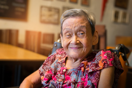 Portrait of a happy elderly woman in colorful dress smiling while sitting in a restaurant.  90 up of healthy woman,front view.