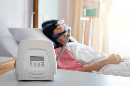 Cpap machine is treating senior patient woman wearing Cpap mask sleeping smoothly without snoring in hospital room.Obstructive sleep apnea therapy. Banque d'images - 133571283