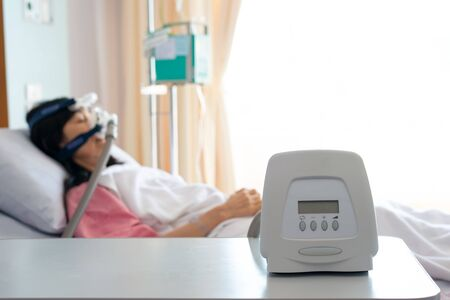 Cpap machine is treating senior patient woman wearing Cpap mask sleeping smoothly without snoring in hospital room.Obstructive sleep apnea therapy.